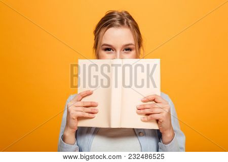 Image of happy young lady student standing isolated over yellow background covering face with book. Looking camera.