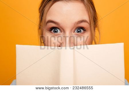 Photo of shocked young lady student standing isolated over yellow background covering face with book. Looking camera.