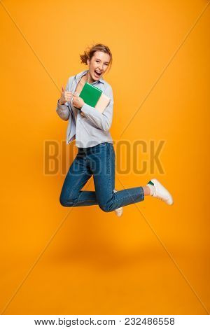 Image of happy young lady student jumping isolated over yellow background holding book. Looking camera showing thumbs up.