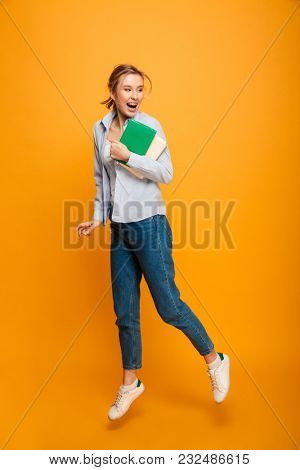 Image of happy young lady student standing isolated over yellow background holding book. Looking aside.