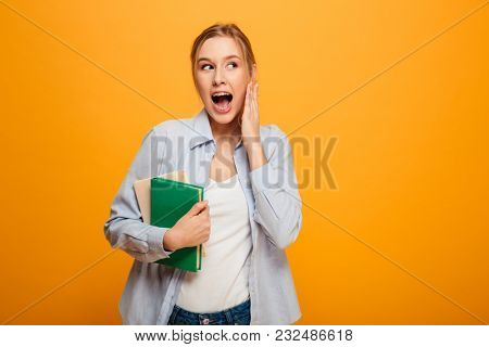 Photo of screaming young woman student standing isolated over yellow background. Looking aside holding books.