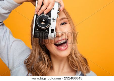Close up portrait of a joyful young girl with braces taking a picture with photo camera isolated over yellow background