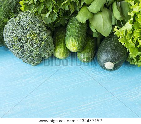 Green Vegetables On A Blue Wooden Background. Parsley, Spinach, Cucumber, Broccoli, Dill And Zucchin