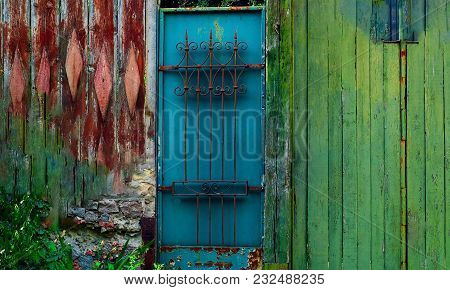 Authentic Wooden Colored Fence And Iron Doors With Wrought Iron Grating, Natural Light, Close-up