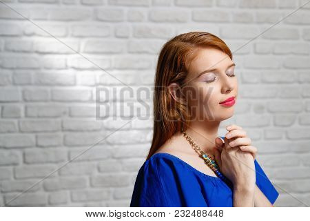 Portrait Of Happy Woman Smiling And Saying Prayer. Redhead Girl Looking Up While Praying. Copy Space