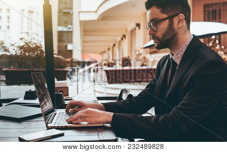Side View Of A Serious Bearded Man Entrepreneur Sitting With Laptop Outdoors In A Bar And Doing Remo
