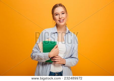 Photo of cheerful young lady student standing isolated over yellow background. Looking camera holding books.