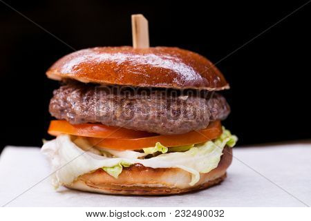 Tasty grilled prawn and beef burger with lettuce and mayonnaise served on pieces of white paper on a rustic wooden table of counter, with copyspace