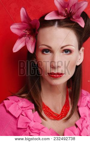 Portrait Of Woman With Dark Brown Hair In Pink Dress. Isolated On Red Background
