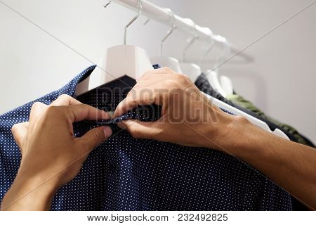closeup of a young caucasian man fastening or unfastening the buttons of a shirt hanging on the rack of a closet