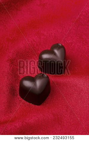 Black Chocolate Hearts On A Red Fabric Background