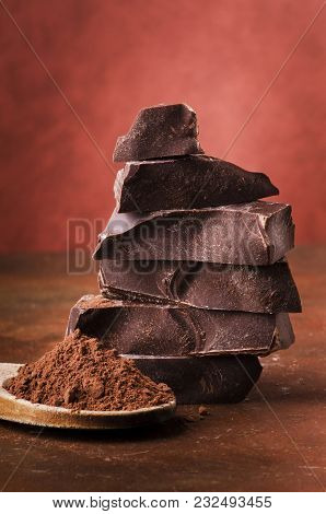 Stacked Pieces Of Dark Chocolate And Cocoa Powder On A Brown Background