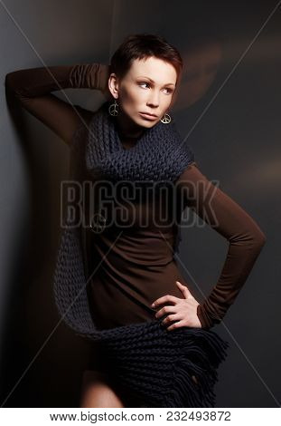 Middle Age Woman In Brown Clothing And Blue Srarf Posing In Studio On Dark Grey Background