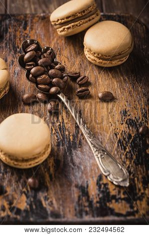 French Coffee Macaroons With Ganache Filling And Spoon With Coffee Beans On Old Wooden Board On Rvin