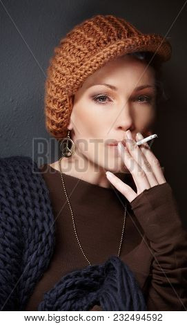Portrait Of Woman With Cigarette In Brown Sweater And Blue Scarf.