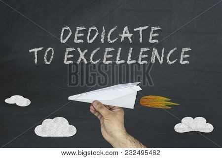 Flying Airplane And Dedicated To Excellence Written On Chalkboard.