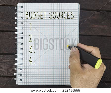 Male Hand Is Writing Budget Sources On A Notepad On A Wooden Table