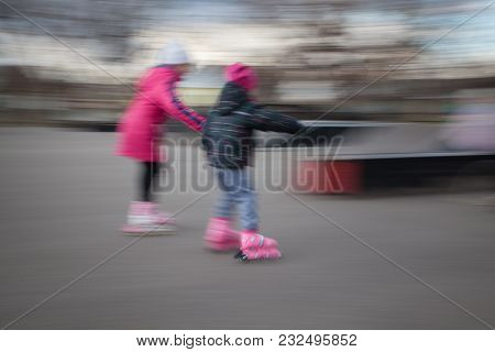 Two Girls Are Rollerblading. They Are Looking Away.