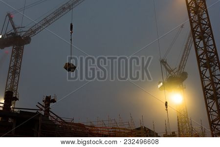 Construction Site At Foggy Evening With Cranes