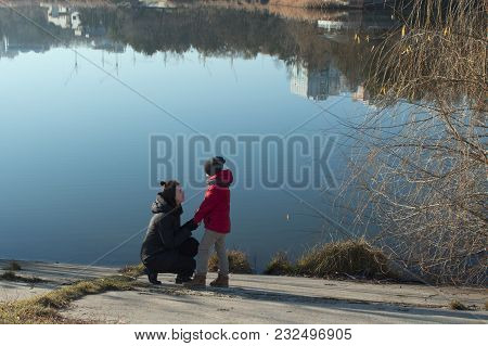 On The Shore Of Lake Mom Talks To Her Son. Family Walking In The Park Near Lake. Mother And Son Look