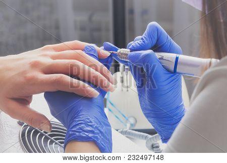 Professional Manicure Process In Beauty Salon. Closeup Manicurist With A Milling Cutter For Manicure