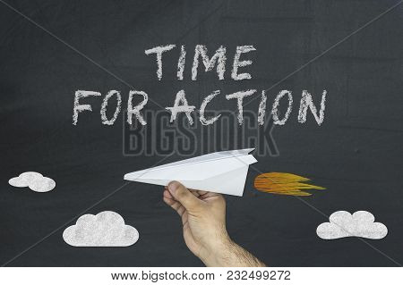 Hand Holding Paper Airplane And Text Written On Blackboard: Time For Action.