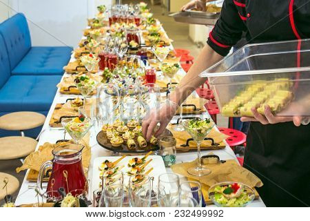 Waiter Serving Table With Delicious And Appetizers. Catering Service