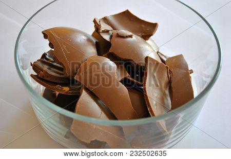 Cracked Eggs Chocolate Of Glass Container, White Background. Milk Chocolate.