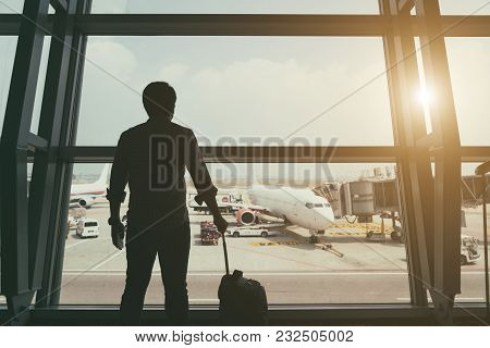 Back Side Of Traveler Boy In Termainal At Airport Looking At The Flying Plane Above Airport, Travel