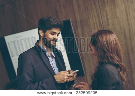 Two Business Colleagues Speaking In An Office On Coffee Break