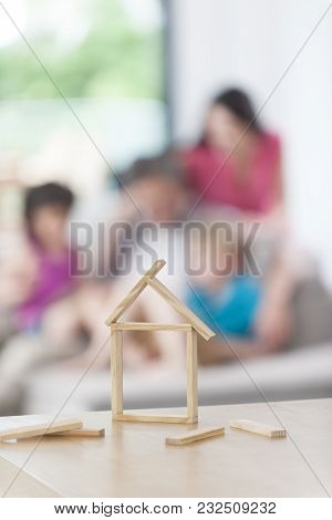 Closeup On A Model House With A Family In The Background.