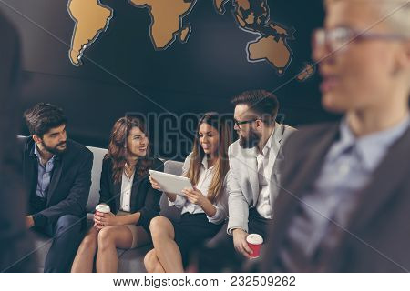 Businessman And Businesswoman Speaking In The Foreground Blurred While Business Team Is Working In T