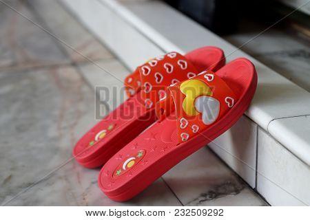 Red Slipper On Concrete Ground, Beside View Of Slipper