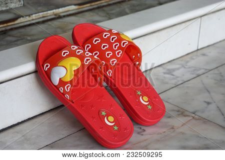 Red Slipper On Concrete Ground, Front View Of Slipper