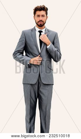 Man in suit straightens collar, portrait on white background