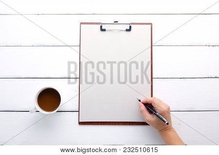 Hand Holding Pen Over Clipboard With Blank Recycle Paper And Coffee Cup On Vintage White Wood Backgr