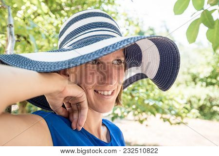 Woman Standing Outdoors In A Stylish Wide Brimmed Blue And White Sunhat In The Shade Of A Garden Tre