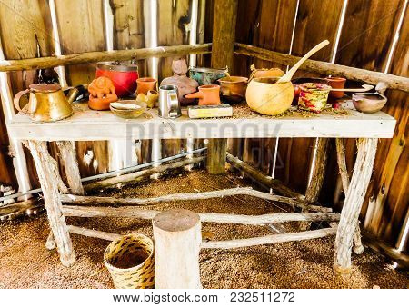 Native American Handmade Wooden Table With Tree Stump For A Seat, Woven Baskets, Clay Pots And Tin C