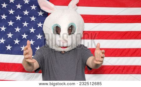 A man wears a Easter Bunny or White Rabbit mask while posing in front of an American Flag in a Photo Booth. Photo Booths are popular at Weddings and all Parties. Everyone loves a good photo booth.