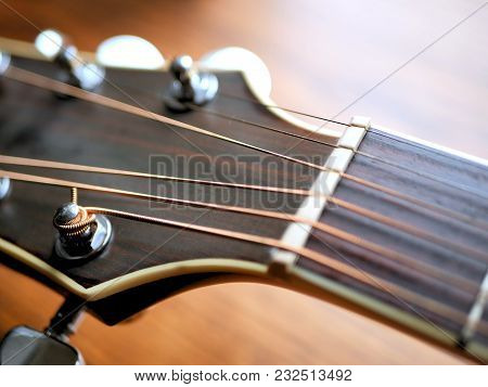 Acoustic Wood Guitar Close Up On Wooden Background With Fretboard, Strings, And Tuners For Music Blo
