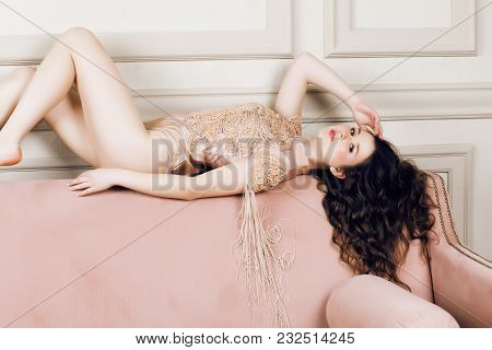 Young Pretty Brunette Girl In Fashion Dress On Sofa Posing In Luxury Rich Home Interior, Lifestyle M