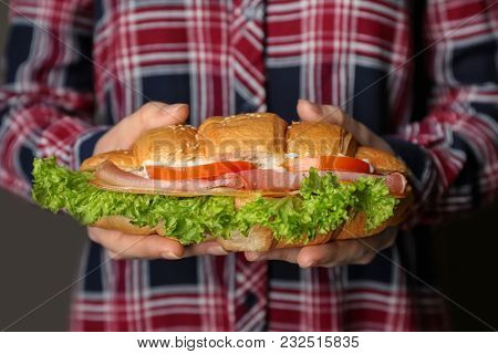 Woman holding tasty croissant sandwich, closeup