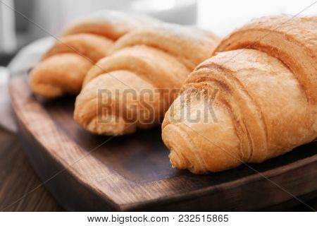 Tasty croissants on wooden tray, closeup