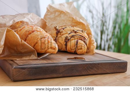 Tasty croissants on wooden board