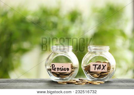 Glass jars with coins on table against blurred background. Pension planning concept