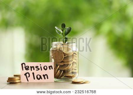 Plant growing from glass jar with coins on table against blurred background. Pension planning concept