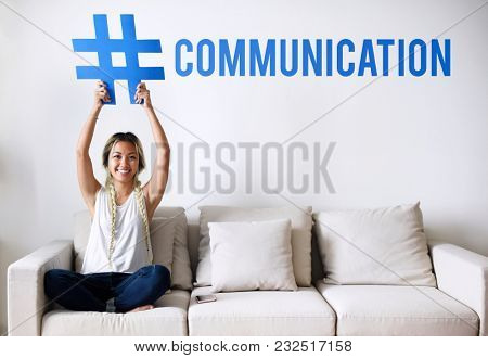 Woman on a couch holding a word