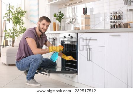 Young man cleaning oven in kitchen