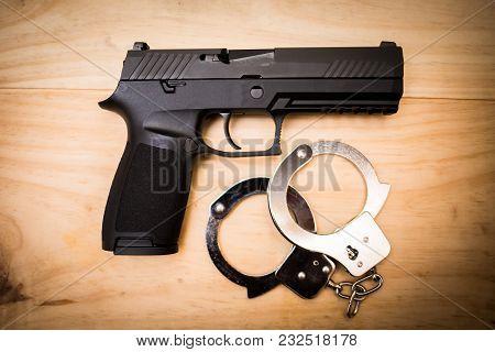 Hand Gun With Hand Cuffs On Wooden Surface