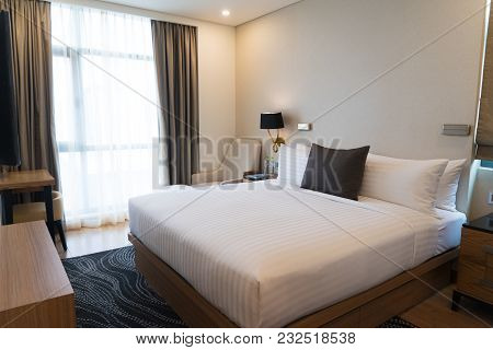 Small Bedroom With Curtains And Modern Furniture. Comfortable Hotel Room With Big Bed, Table And Car